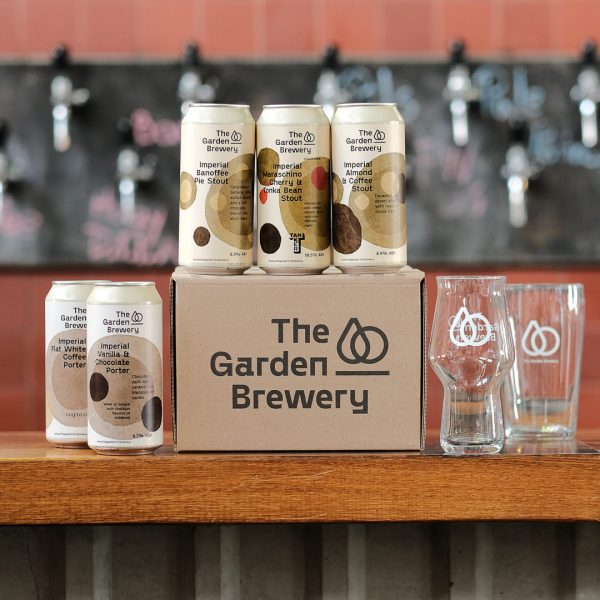 The Garden Brewery box with craft dark beer cans on top, two cans on the side and craft master glass.